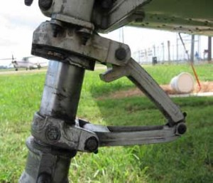 You can see the protrusion on the forward end of the upper torque link. As the strut extents and the scissors straighten out, the protrusion makes contact with the a flat spot on the strut causing the nose gear to center